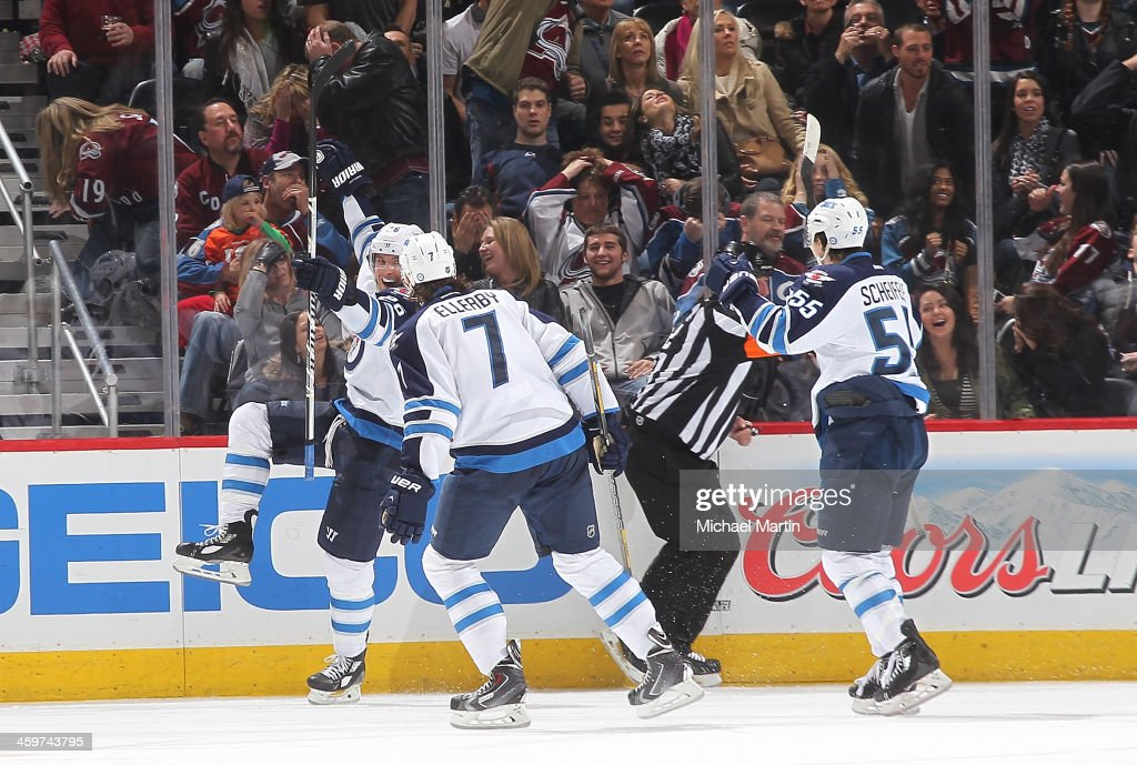 Blake Wheeler #26, Mark Scheifele #55, and Keaton Ellerby #7 of the Winnipeg Jets celebrates the game winning goal with less then a second to play in overtime against the Colorado Avalanche at the Pepsi Center on December 29, 2013 in Denver, Colorado.ÊThe Jets defeated the avalanche 2-1 in overtime.