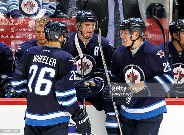 Blake Wheeler Mark Scheifele and Patrik Laine of the Winnipeg Jets share a laugh during a second period stoppage in play against the Dallas Stars at...