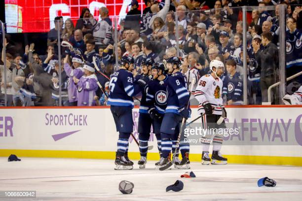 Blake Wheeler Mark Scheifele Nikolaj Ehlers and Jacob Trouba of the Winnipeg Jets celebrate Ehler's third period hat trick goal against the Chicago...