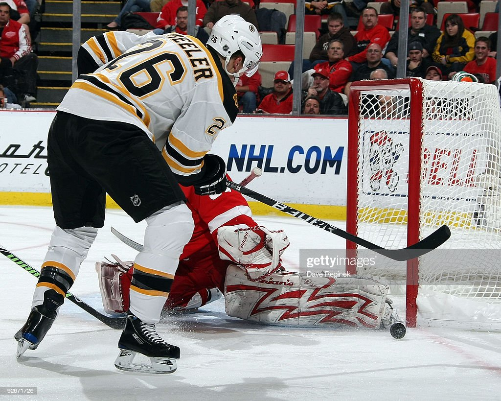 Blake Wheeler #26 of the Boston Bruins looks for the loose puck as Chris Osgood #30 of the Detroit Red Wings gets into position to make a save during a NHL game at Joe Louis Arena on November 3, 2009 in Detroit, Michigan.