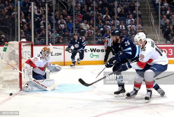 Blake Wheeler of the Winnipeg Jets and Aleksander Barkov of the Florida Panthers watch as the puck slides past goaltender James Reimer during second...