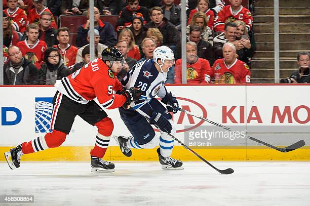 Blake Wheeler of the Winnipeg Jets and David Rundblad of the Chicago Blackhawks skate up the boards during the NHL game on November 02 2014 at the...