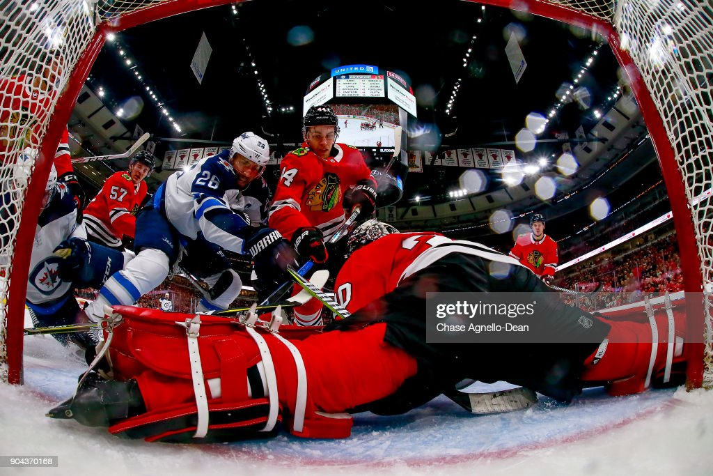 Blake Wheeler #26 of the Winnipeg Jets and Jan Rutta #44 of the Chicago Blackhawks work to get at the puck covered by goalie Jeff Glass #30 at the United Center on January 12, 2018 in Chicago, Illinois.