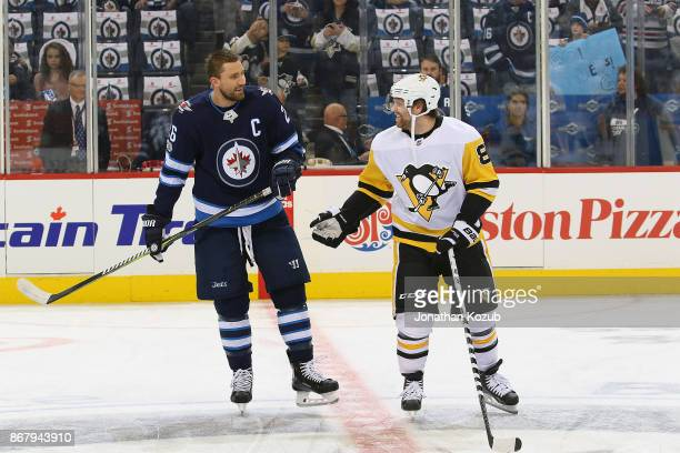 Blake Wheeler of the Winnipeg Jets and Phil Kessel of the Pittsburgh Penguins share a laugh during the pregame warm up prior to NHL action at the...