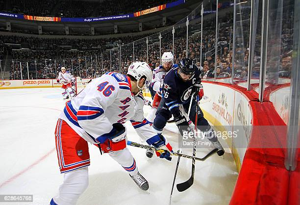 Blake Wheeler of the Winnipeg Jets battles for possession of the puck against Marek Hrivik and Kevin Klein of the New York Rangers during first...