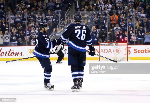 Blake Wheeler of the Winnipeg Jets celebrates his empty net goal against the Dallas Stars with teammate Bryan Little at the MTS Centre on February 14...