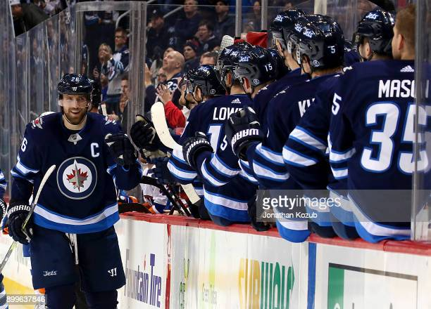 Blake Wheeler of the Winnipeg Jets celebrates his first period goal against the New York Islanders with teammates at the bench at the Bell MTS Place...