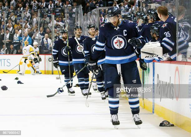 Blake Wheeler of the Winnipeg Jets celebrates his first period hat trick against the Pittsburgh Penguins as hats rain down on the ice at the Bell MTS...