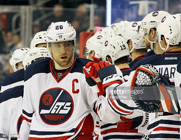 Blake Wheeler of the Winnipeg Jets celebrates his third period goal against the Calgary Flames with teammates at the bench at the MTS Centre on...