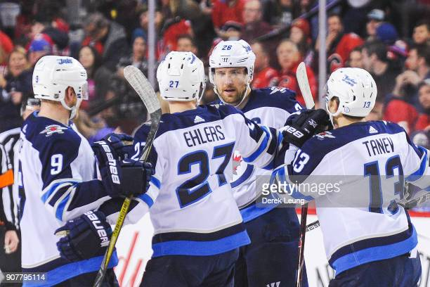 Blake Wheeler of the Winnipeg Jets celebrates with his teammates after scoring against the Calgary Flames during a shootout at Scotiabank Saddledome...