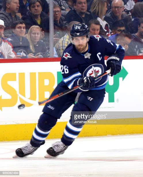 Blake Wheeler of the Winnipeg Jets chips the puck up the ice during second period action against the Chicago Blackhawks at the Bell MTS Place on...