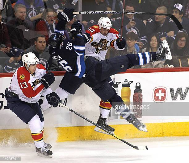 Blake Wheeler of the Winnipeg Jets collides with Erik Gudbranson of the Florida Panthers in NHL action at the MTS Centre on March 1 2012 in Winnipeg...
