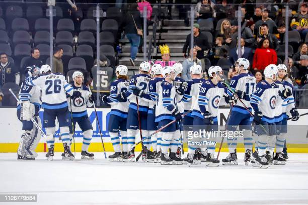 Blake Wheeler of the Winnipeg Jets congratulates goaltender Connor Hellebuyck as teammates celebrate a 63 victory over the Vegas Golden Knights at...