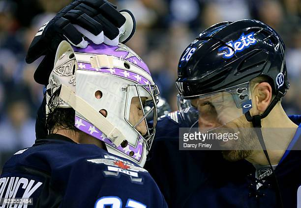 Blake Wheeler of the Winnipeg Jets congratulates goaltender Connor Hellebuyck after a 40 shutout victory over the Chicago Blackhawks at the MTS...