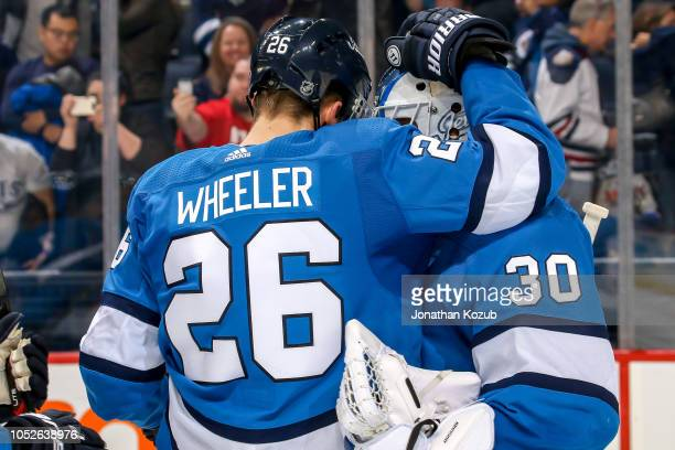 Blake Wheeler of the Winnipeg Jets congratulates goaltender Laurent Brossoit following a 53 victory over the Arizona Coyotes at the Bell MTS Place on...