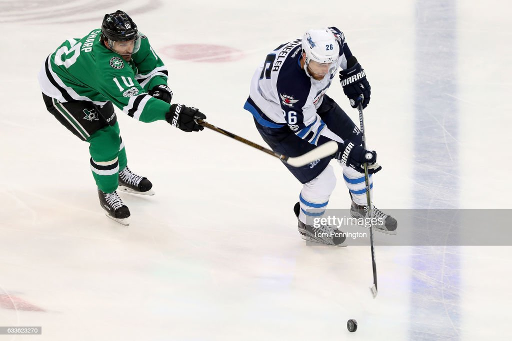 Blake Wheeler #26 of the Winnipeg Jets controls the puck against Patrick Sharp #10 of the Dallas Stars in the third period at American Airlines Center on February 2, 2017 in Dallas, Texas.