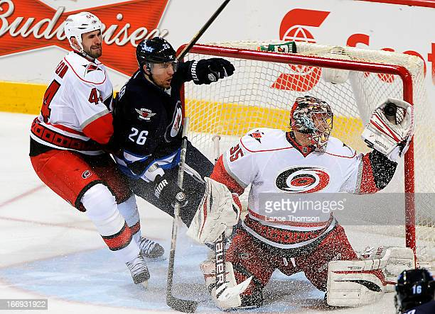 Blake Wheeler of the Winnipeg Jets gets pushed into the crease by Jay Harrison of the Carolina Hurricanes as goaltender Justin Peters makes a glove...