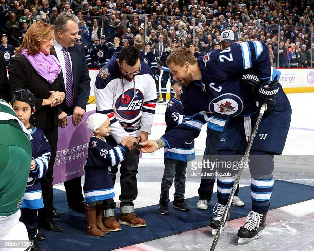 Blake Wheeler of the Winnipeg Jets hands the puck to cancer patient Maia following the ceremonial faceoff on Hockey Fights Cancer night against the...