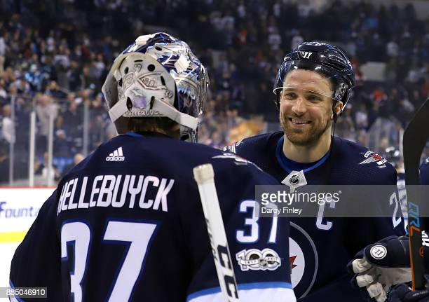 Blake Wheeler of the Winnipeg Jets is all smiles as he congratulates goaltender Connor Hellebuyck following a 50 shutout over the Ottawa Senators at...