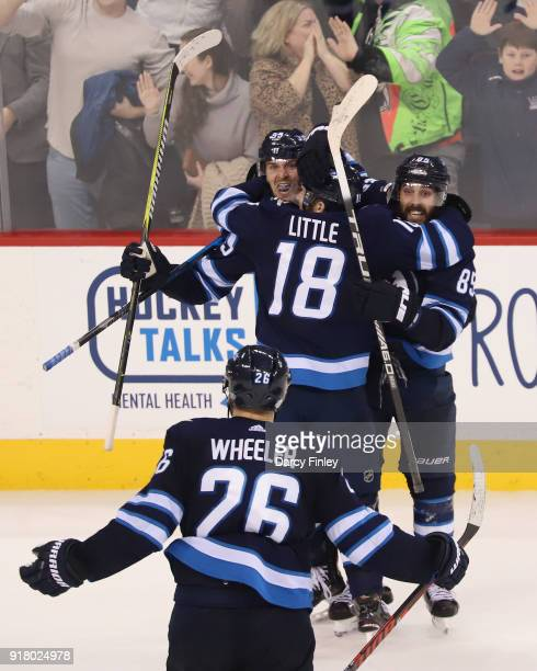 Blake Wheeler of the Winnipeg Jets joins teammates Mark Scheifele Bryan Little and Mathieu Perreault to celebrate a third period goal against the...
