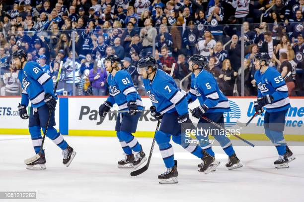 Blake Wheeler of the Winnipeg Jets leads teammates Kyle Connor Ben Chiarot Dmitry Kulikov and Mark Scheifele to the bench after scoring a first...