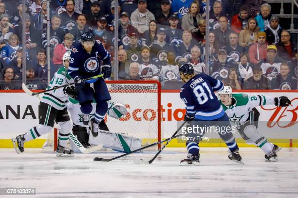 Blake Wheeler of the Winnipeg Jets leaps into the air as he sets a screen for teammate Kyle Connor during third period action against the Dallas...