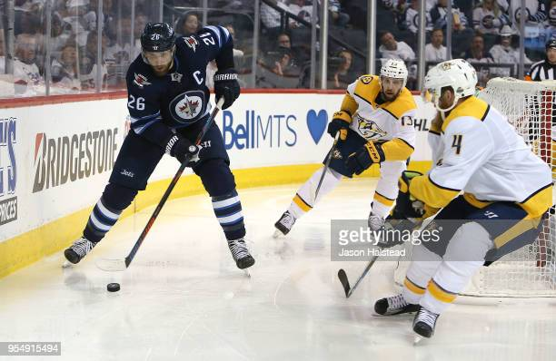 Blake Wheeler of the Winnipeg Jets moves the puck against Ryan Ellis and Nick Bonino of the Nashville Predators in Game Four of the Western...