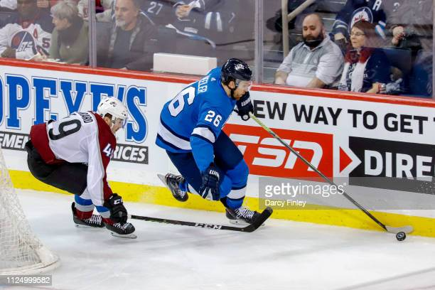 Blake Wheeler of the Winnipeg Jets plays the puck along the boards as Samuel Girard of the Colorado Avalanche gives chase during second period action...