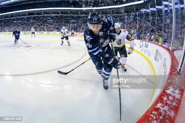 Blake Wheeler of the Winnipeg Jets plays the puck along the boards away from Brayden McNabb of the Vegas Golden Knights during first period action at...