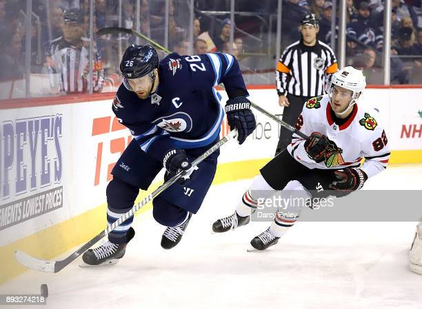 Blake Wheeler of the Winnipeg Jets plays the puck along the boards away from Jordan Oesterle of the Chicago Blackhawks during second period action at...