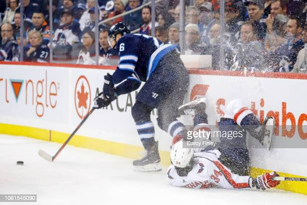 Blake Wheeler of the Winnipeg Jets plays the puck away as Jonas Siegenthaler of the Washington Capitals crashes along the end boards during first...