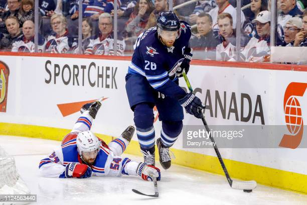 Blake Wheeler of the Winnipeg Jets plays the puck away from a fallen Adam McQuaid of the New York Rangers during third period action at the Bell MTS...