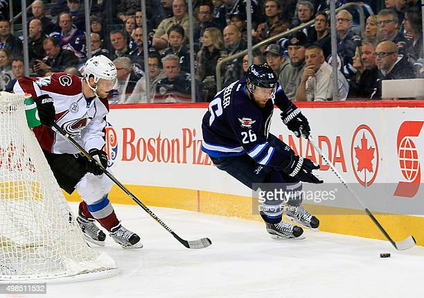 Blake Wheeler of the Winnipeg Jets plays the puck behind the net as Carl Soderberg of the Colorado Avalanche defends during first period action at...