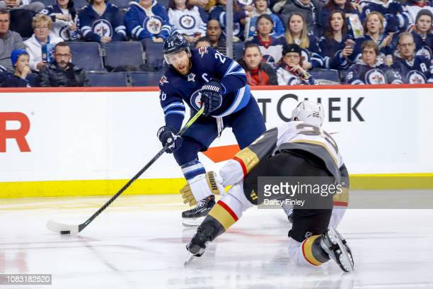Blake Wheeler of the Winnipeg Jets plays the puck down the ice as Nick Holden of the Vegas Golden Knights defends during second period action at the...
