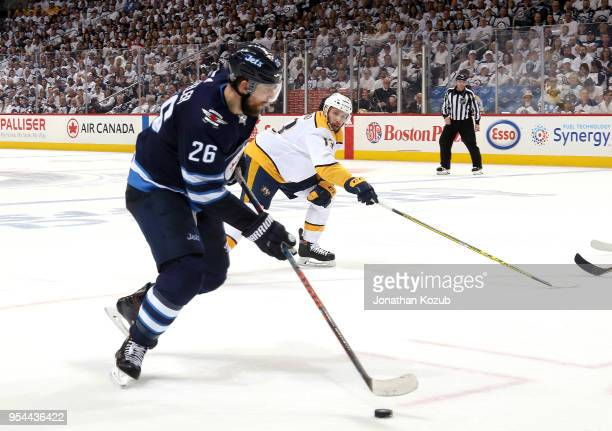 Blake Wheeler of the Winnipeg Jets plays the puck down the ice as Nick Bonino of the Nashville Predators defends during third period action in Game...