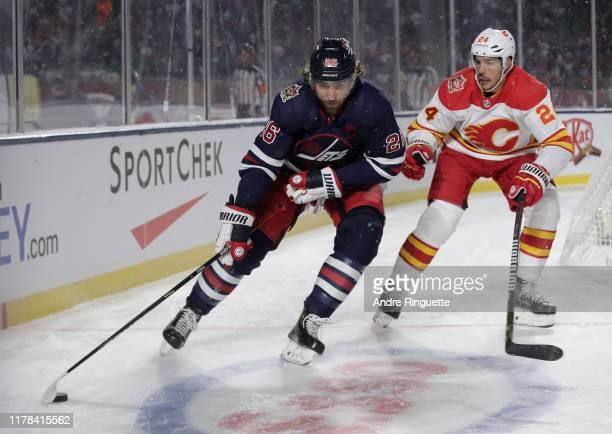 Blake Wheeler of the Winnipeg Jets pulls the puck away from Travis Hamonic of the Calgary Flames during the 2019 Tim Hortons NHL Heritage Classic at...