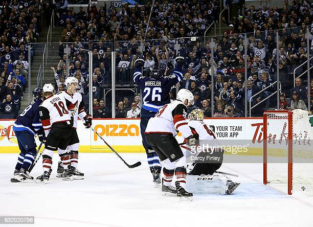 Blake Wheeler of the Winnipeg Jets raises his arms in celebration after teammate Josh Morrissey scores a first period goal against the Arizona...
