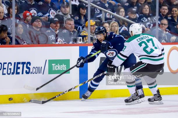 Blake Wheeler of the Winnipeg Jets shoots the puck down the ice as Erik Condra of the Dallas Stars defends during second period action at the Bell...