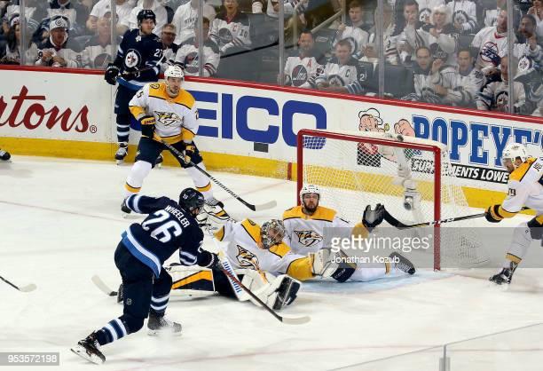 Blake Wheeler of the Winnipeg Jets shoots the puck just over the net as goaltender Pekka Rinne and Nick Bonino of the Nashville Predators sprawl in...