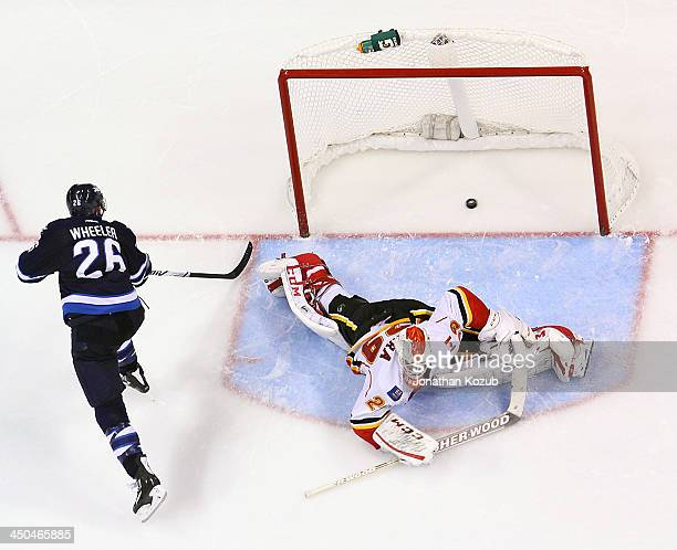 Blake Wheeler of the Winnipeg Jets shoots the puck over a sprawling Reto Berra of the Calgary Flames during the shootout at the MTS Centre on...