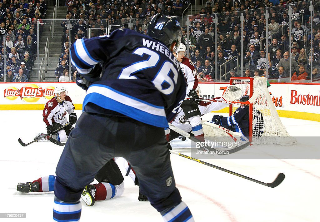 Blake Wheeler #26 of the Winnipeg Jets shoots the puck over the outstretched glove of goaltender Reto Barra #20 of the Colorado Avalanche to score the overtime winner and give the Jets a 5-4 victory at the MTS Centre on March 19, 2014 in Winnipeg, Manitoba, Canada.