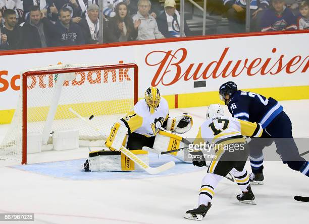 Blake Wheeler of the Winnipeg Jets shoots the puck past goaltender Casey Desmith of the Pittsburgh Penguins for a first period hat trick at the Bell...