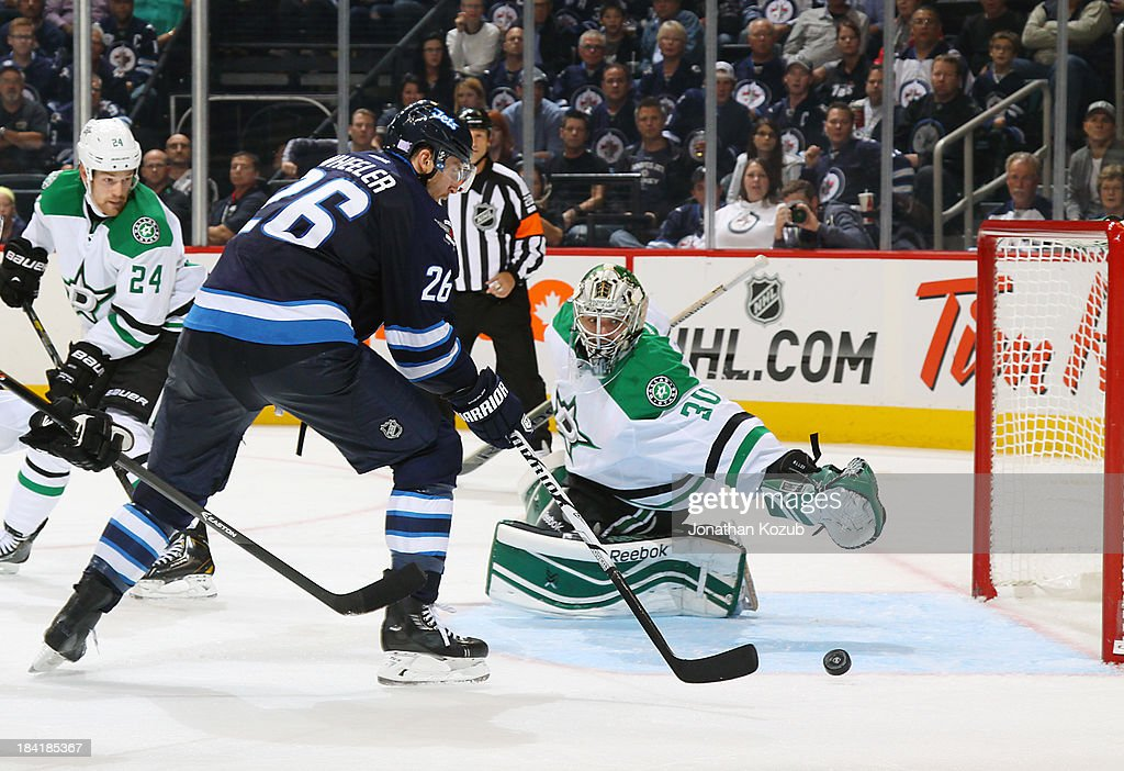 Blake Wheeler #26 of the Winnipeg Jets shoots the puck towards the open net for a third period goal as goaltender Dan Ellis #30 of the Dallas Stars dives across the crease at the MTS Centre on October 11, 2013 in Winnipeg, Manitoba, Canada.