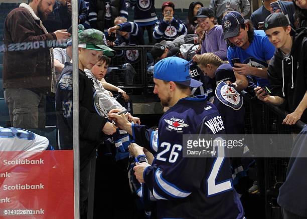 Blake Wheeler of the Winnipeg Jets signs autographs for fans following NHL action against the Edmonton Oilers on Canadian Forces Appreciation Night...