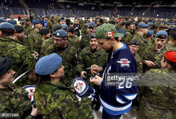 Blake Wheeler of the Winnipeg Jets signs autographs for members of the Canadian Armed Forces following NHL action against the Arizona Coyotes on...