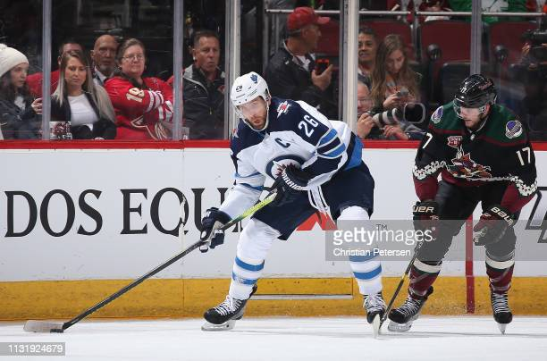 Blake Wheeler of the Winnipeg Jets skates with the puck ahead of Alex Galchenyuk of the Arizona Coyotes during the first period of the NHL game at...