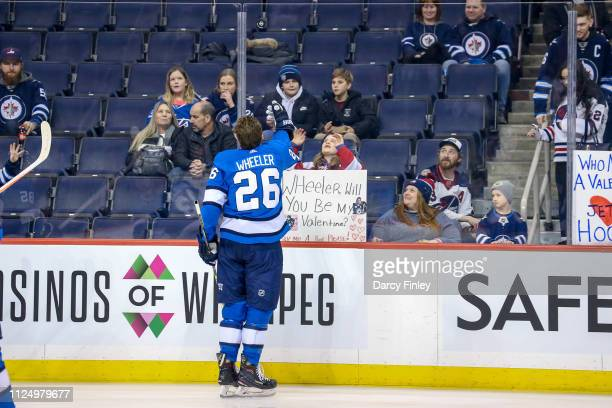 Blake Wheeler of the Winnipeg Jets throws a puck over the glass to a fan during the pregame warm up prior to NHL action against the Colorado...