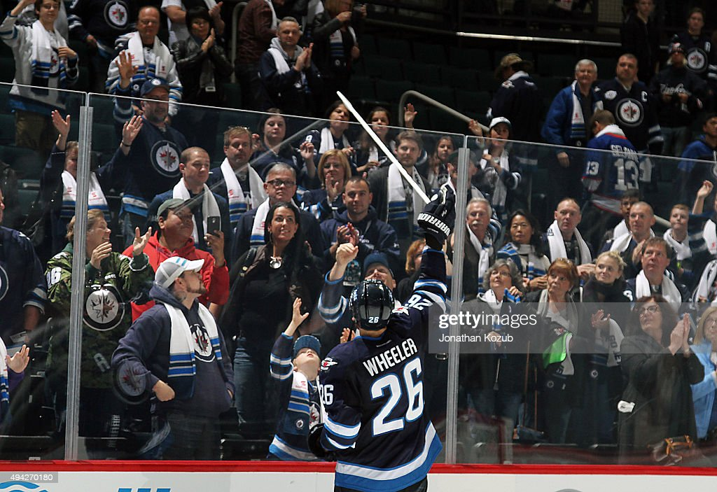 Blake Wheeler #26 of the Winnipeg Jets throws his stick over the glass to a young fan after receiving second star honors following a 5-4 victory over the Minnesota Wild at the MTS Centre on October 25, 2015 in Winnipeg, Manitoba, Canada. Wheeler had two assists to become the first player in franchise history to post a point in each of the first eight games of the season.