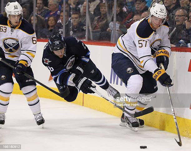 Blake Wheeler of the Winnipeg Jets trips battling with Tyler Ennis and Tyler Myers for the puck during second period action on April 9 2013 at the...