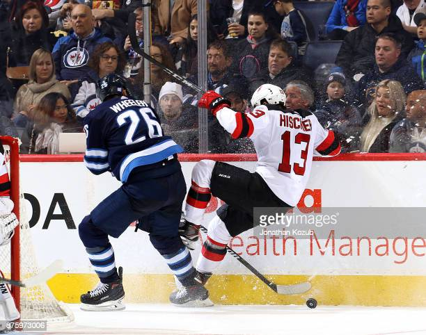 Blake Wheeler of the Winnipeg Jets trips up Nico Hischier of the New Jersey Devils as they battle along the boards for the puck during third period...